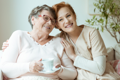 happy senior woman with female caregiver