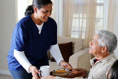 female caregiver serving food to senior man