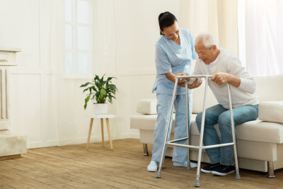 caregiver assisting senior man in his house